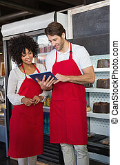 Smiling colleagues in red apron using tablet together