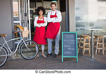 Smiling colleagues in red apron