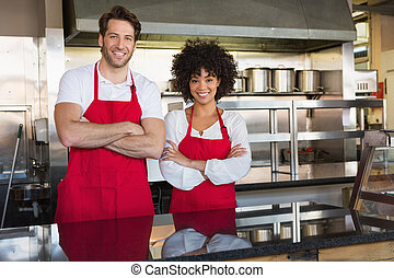 Smiling colleagues in red apron with arms crossed