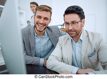 smiling colleagues looking at the computer monitor