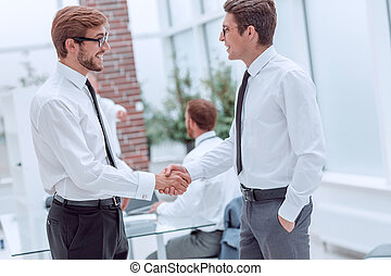 smiling colleagues shaking hands in the office