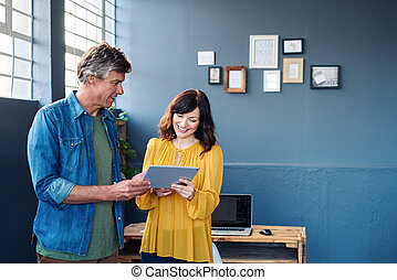 Smiling colleagues talking together over a tablet in an office