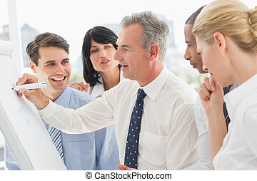 Smiling colleagues watching businessman writing on whiteboard