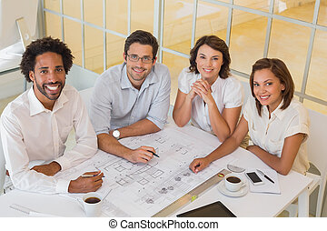 Smiling colleagues working on blueprints in office