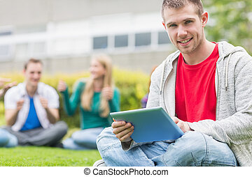 Smiling college boy holding tablet PC with students in park...