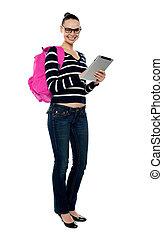 Smiling college girl using tablet pc, full length portrait