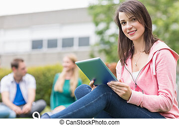 Smiling college girl using tablet PC with students in park