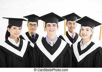 smiling college graduate at graduation with classmates