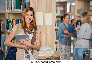 Smiling college student holding tablet in library