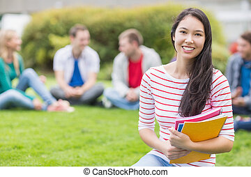 Smiling college student with blurred friends in the park -...