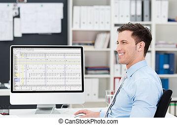 Smiling confident businessman at his desk