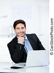 Smiling confident businessman in the office