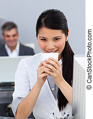 Smiling confident Businesswoman drinking a coffee at her desk