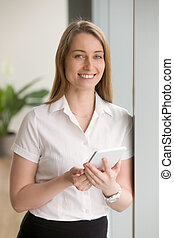 Smiling confident businesswoman holding digital tablet looking a