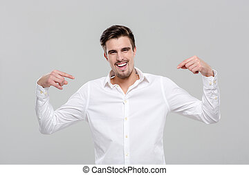 Smiling confident man pointing on himself