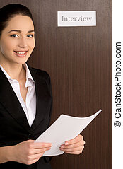 Smiling confident woman standing with CV. Getting ready for...
