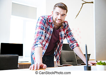 Smiling confident young male with beard standing in office -...