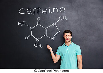Smiling confident young student showing chemical structure of caffeine molecule