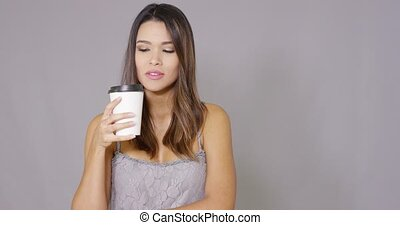 Smiling confident young woman drinking coffee