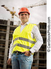 Smiling construction engineer in hardhat looking at camera