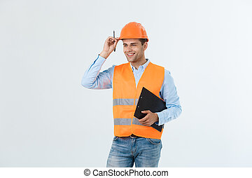 Smiling construction engineer posing isolated over grey background