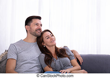 Contemplated Couple Sitting On Couch At Home