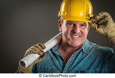 Smiling Contractor in Hard Hat Holding Floor Plans With Dramatic Lighting.