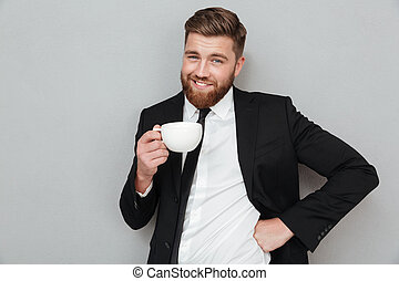 Smiling cool bearded man in suit holding cup of coffee