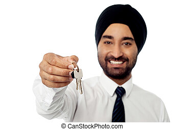 Smiling corporate guy holding a house key