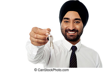 Smiling corporate guy holding a key