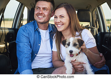 Smiling couple and their dog sitting in the car trunk