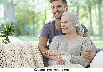 Smiling couple at home. Husband supporting sick wife after chemotherapy