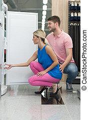 Smiling Couple Buying A Fridge In Supermarket - Beautiful...