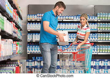 Smiling Couple Buying Dairy Products In Supermarket -...