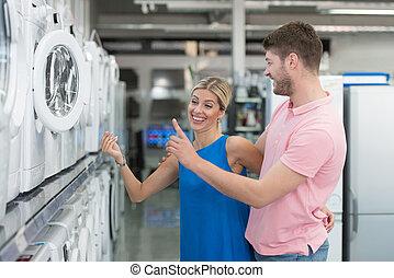 Smiling Couple Buying Washing Machine In Supermarket -...
