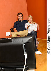 Smiling couple changing channels watching television evening