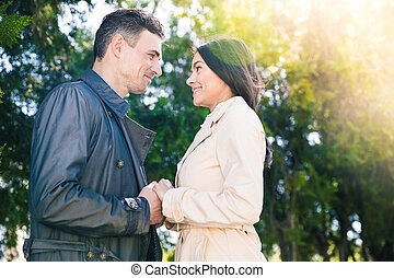 Smiling couple dating in park - Smiling couple dating and...