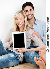 Smiling couple displaying a tablet-pc screen