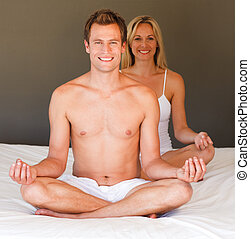 Smiling couple doing exercises on bed