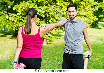 smiling couple doing streching in the park