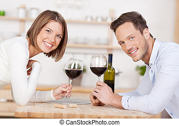 Smiling couple drink red wine
