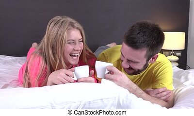 Smiling couple drinking coffee lying in the bed, closeup