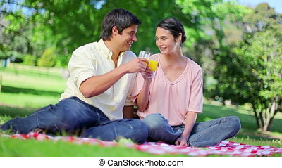 Smiling couple drinking glasses of orange juice