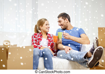 smiling couple drinking tea or coffee at new home