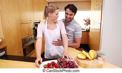 Smiling couple eating fruits