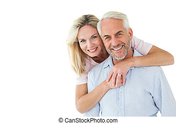 Smiling couple embracing and looking at camera on white...