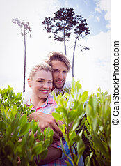 Smiling couple embracing outside among the bushes