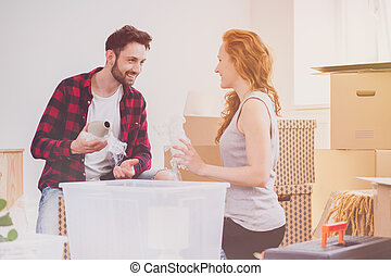 Smiling couple enjoying packing stuff while moving-into new home