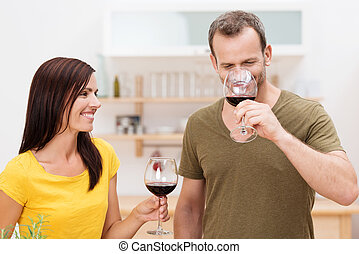 Smiling couple enjoying red wine in the kitchen