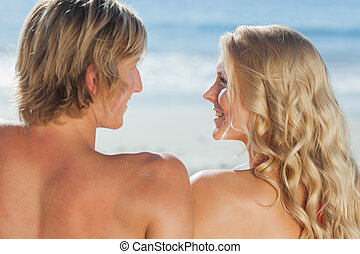 Smiling couple facing each other on the beach